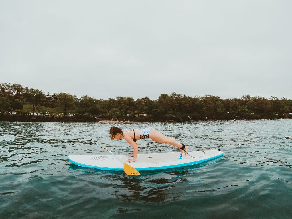 Attempting SUP yoga on a stand up paddle boarding tour with Maui SUP